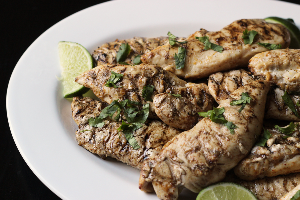 A plate of grilled chicken with lime wedges