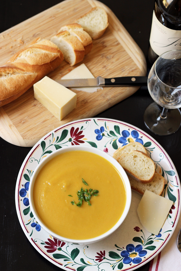 a plate of food, bowl of soup, bread and cheese