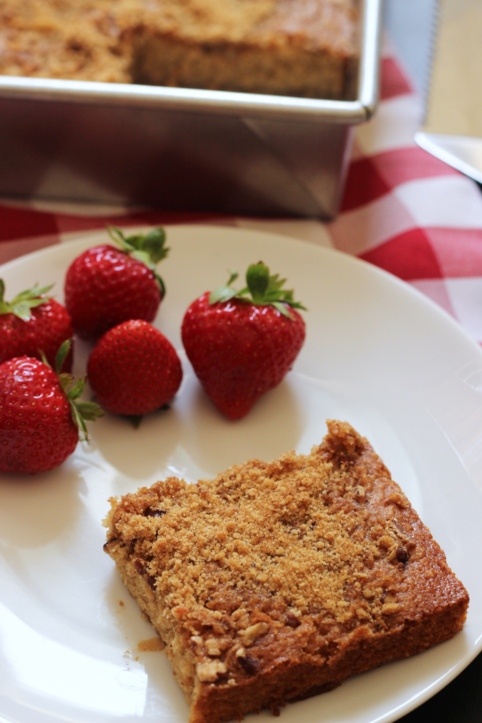 square of banana pecan coffeecake on a plate with strawberries