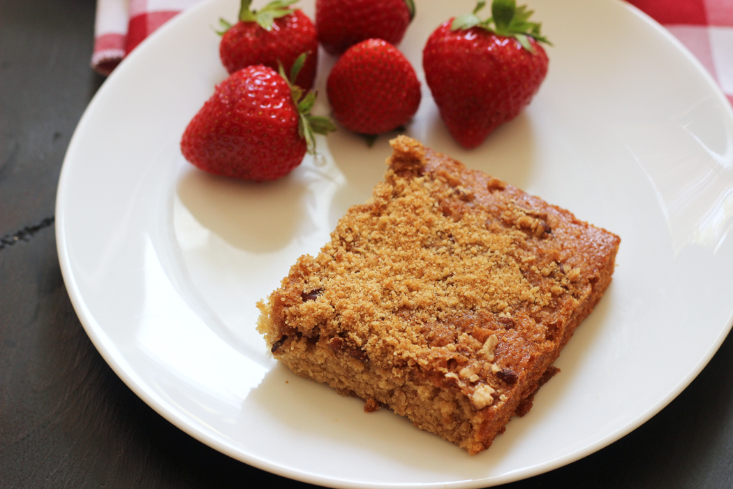 white plate with square of banana pecan coffeecake and strawberries