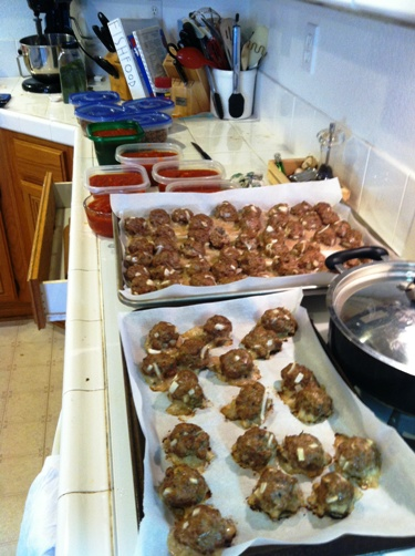 trays of baked meatballs and containers of sauce