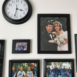 clock on wall surrounded by family photos