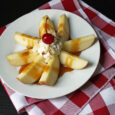 sliced apple with caramel sauce, whipped cream, and cherry