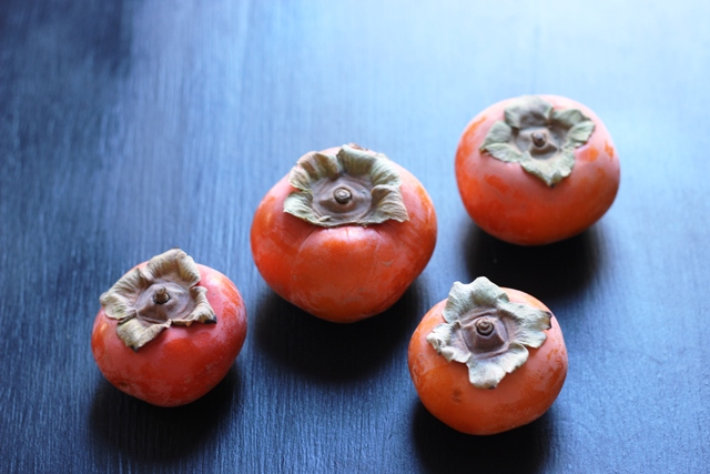 four persimmons on a black table top