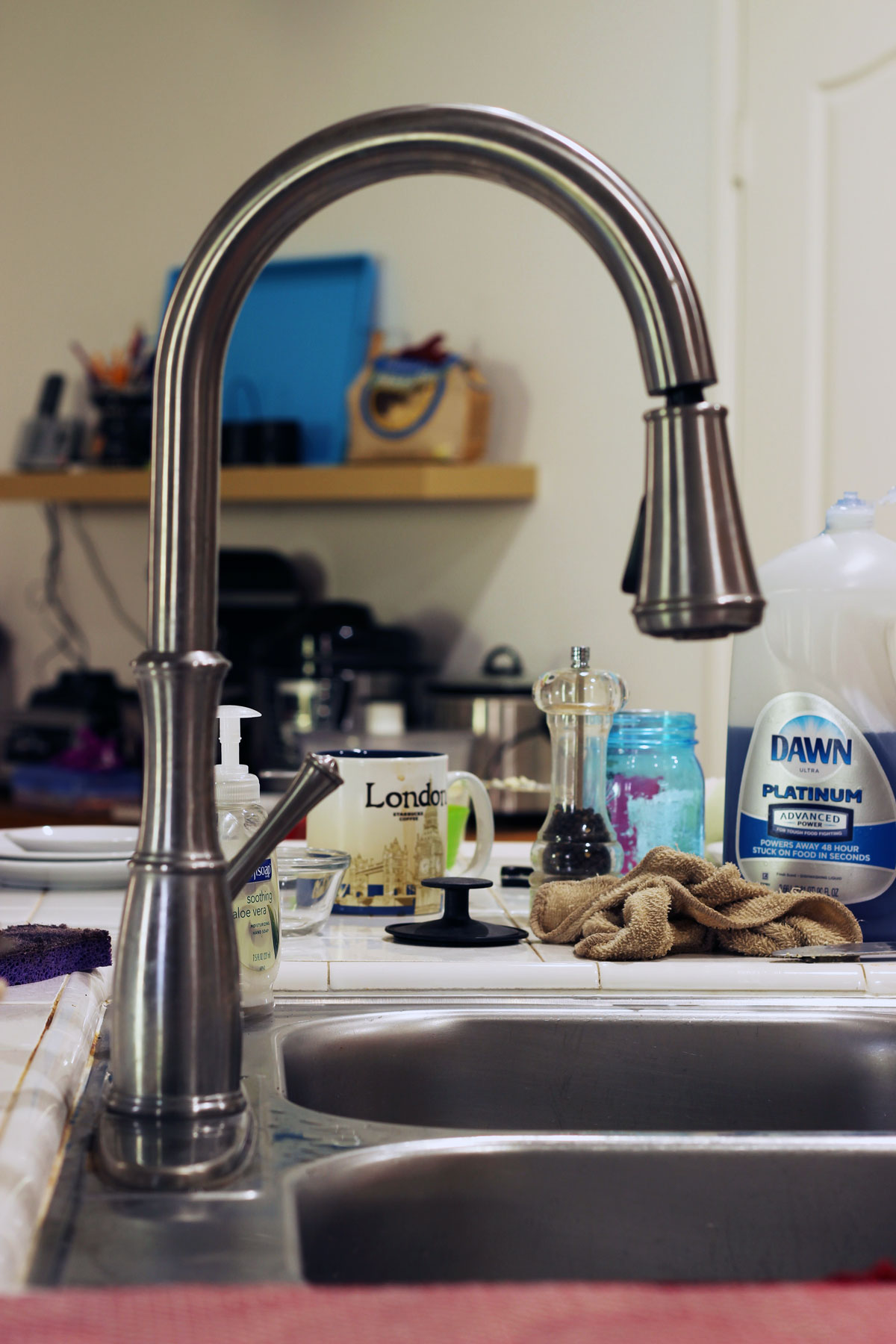 clutter on counter by kitchen sink
