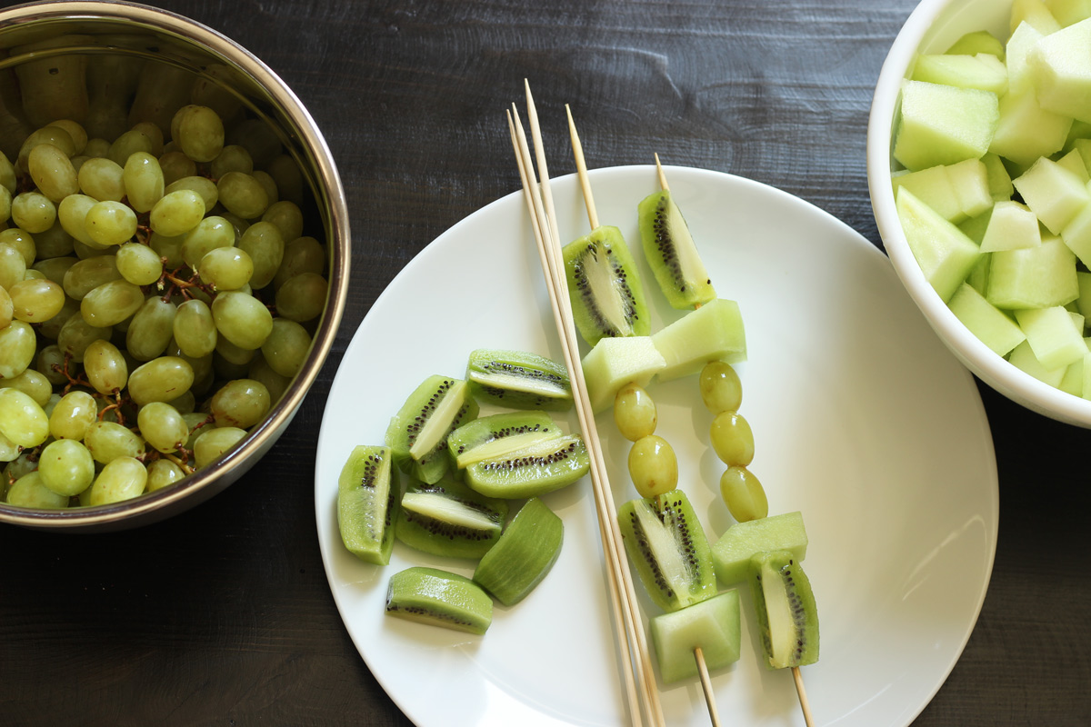 platter of green fruit kabobs with bowls of fruit