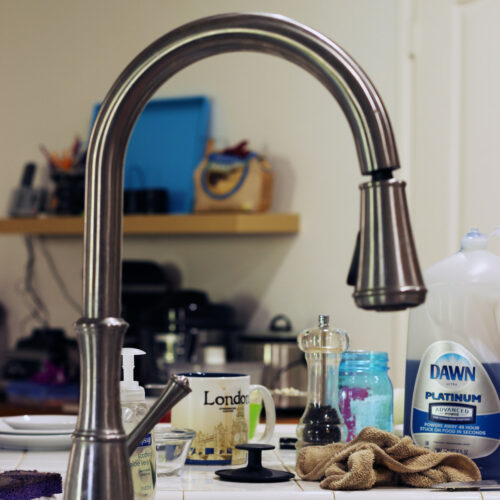 view of clutter behind kitchen faucet
