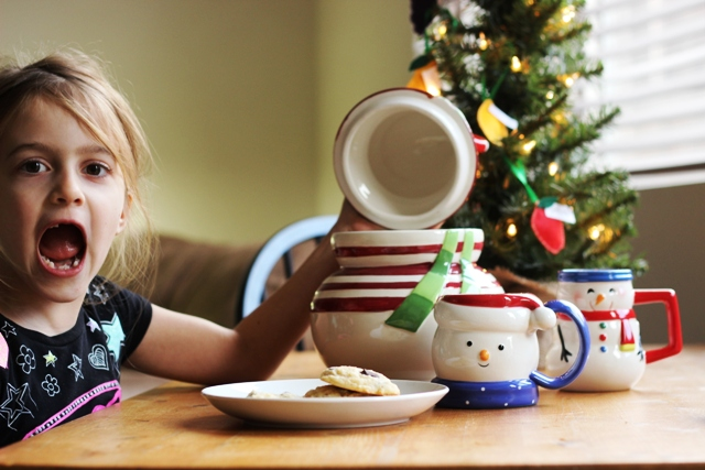 A little girl sitting at a table with cookies and christmas mug