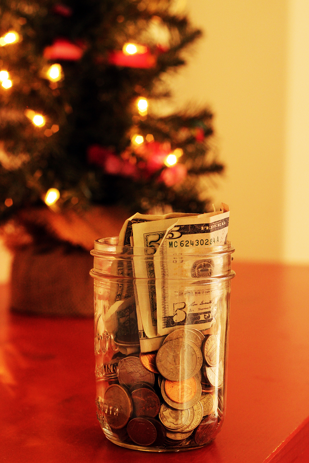 jar of money savings in front of small lit christmas tree