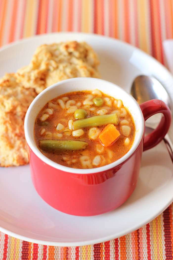 A mug of soup on plate with biscuits