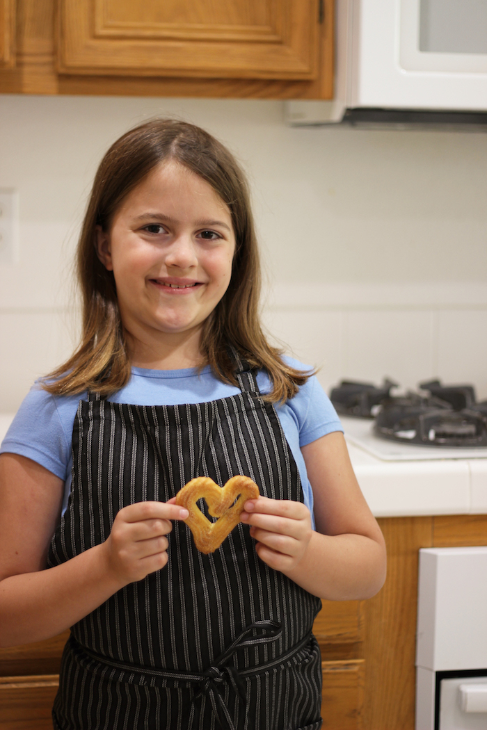 A girl standing in the kitchen with heart cookie