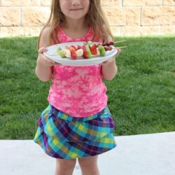 girl with fruit kabobs