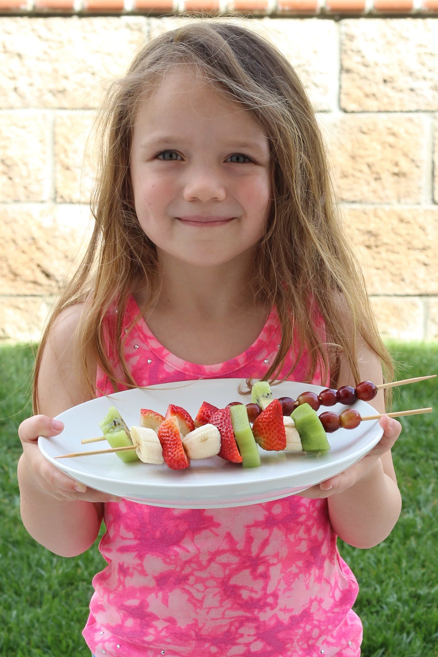 A little girl holding a platter of fruit skewers
