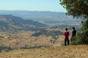 boys on hilltop with view
