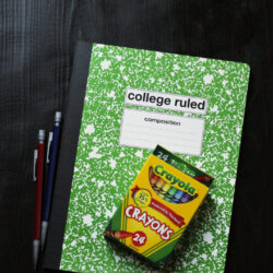 green composition book with a box of crayons and pencils