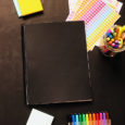 black covered planner with pens stickers and post-its