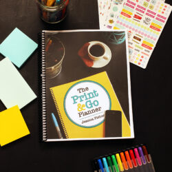 print and go planner on black table with pens post-its and stickers