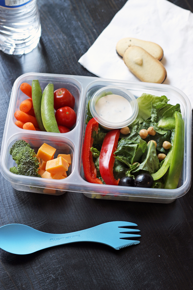 divided lunch box with veggies cheese fruit and dip