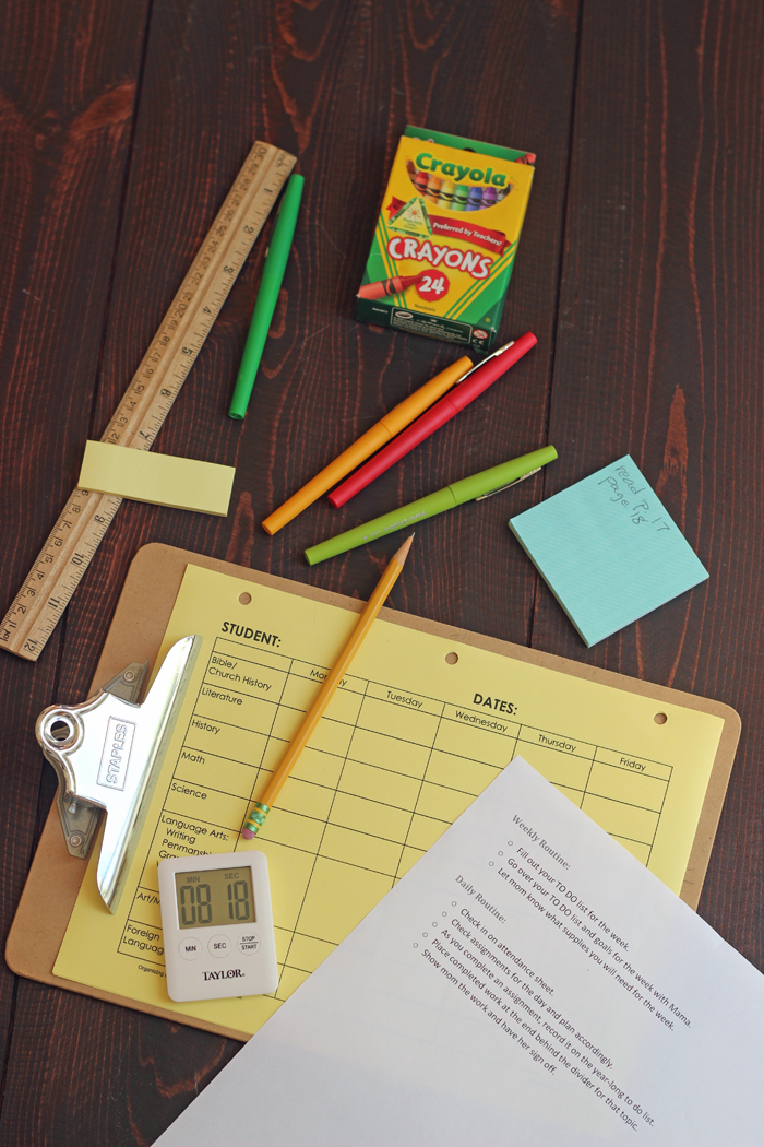clipboard, pencils, timer, and crayons on tabletop
