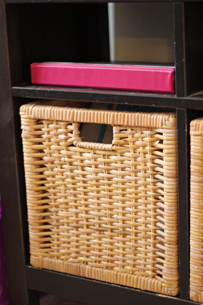 basket in bottom cubby with pink binder in top cubby