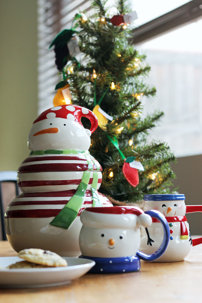 snowman mug next to a small Christmas tree