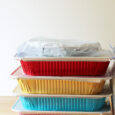 stack of colored aluminum baking pans with lids