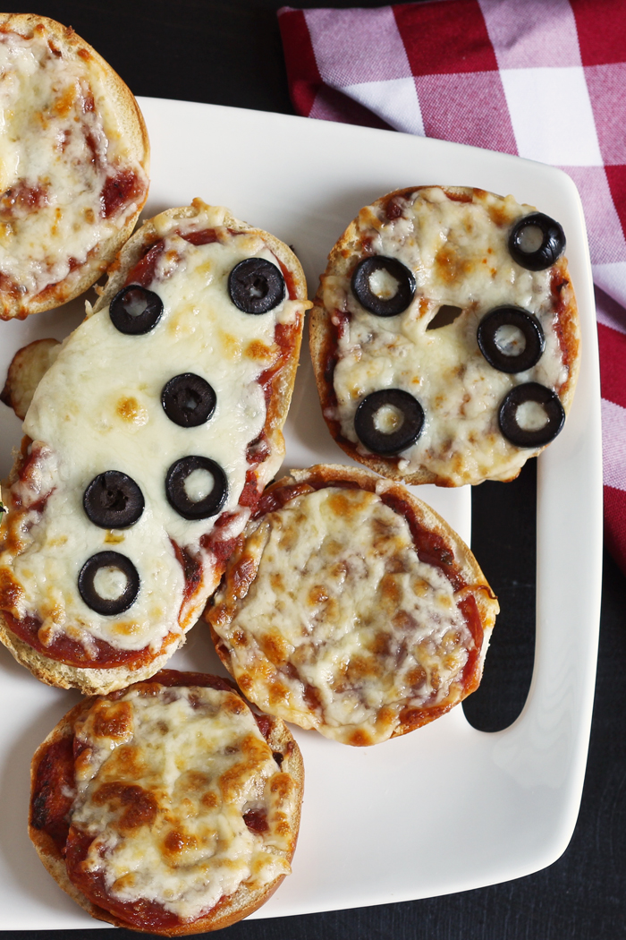 A plate of bagel and french bread pizzas