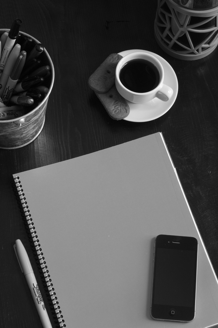 black and white planner with phone, pens, and coffee