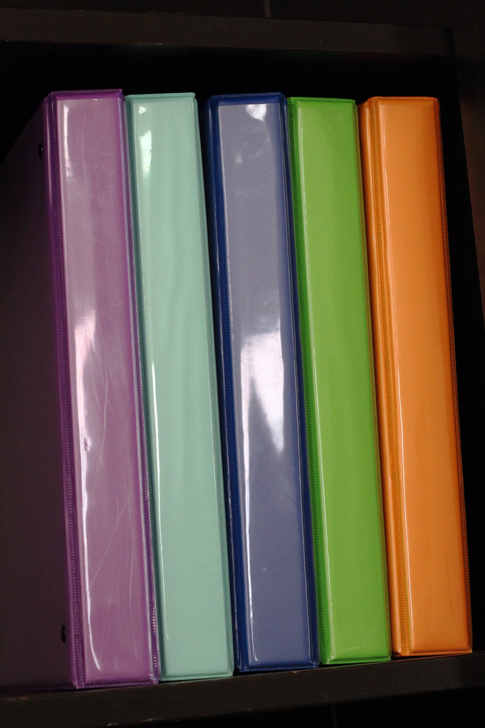 many colored binders on a shelf