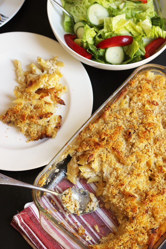 baking dish of noodle casserole with bowl of salad and dinner plate