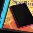 pink kindle on stack of school books