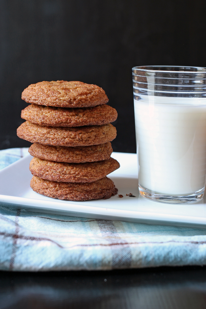 cookies stacked on a white tray with a glass of milk