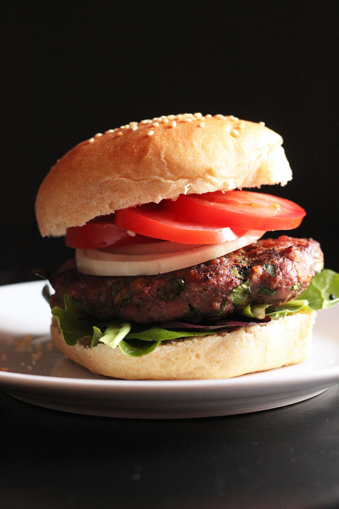 A close up of a Hamburger with tomatoes