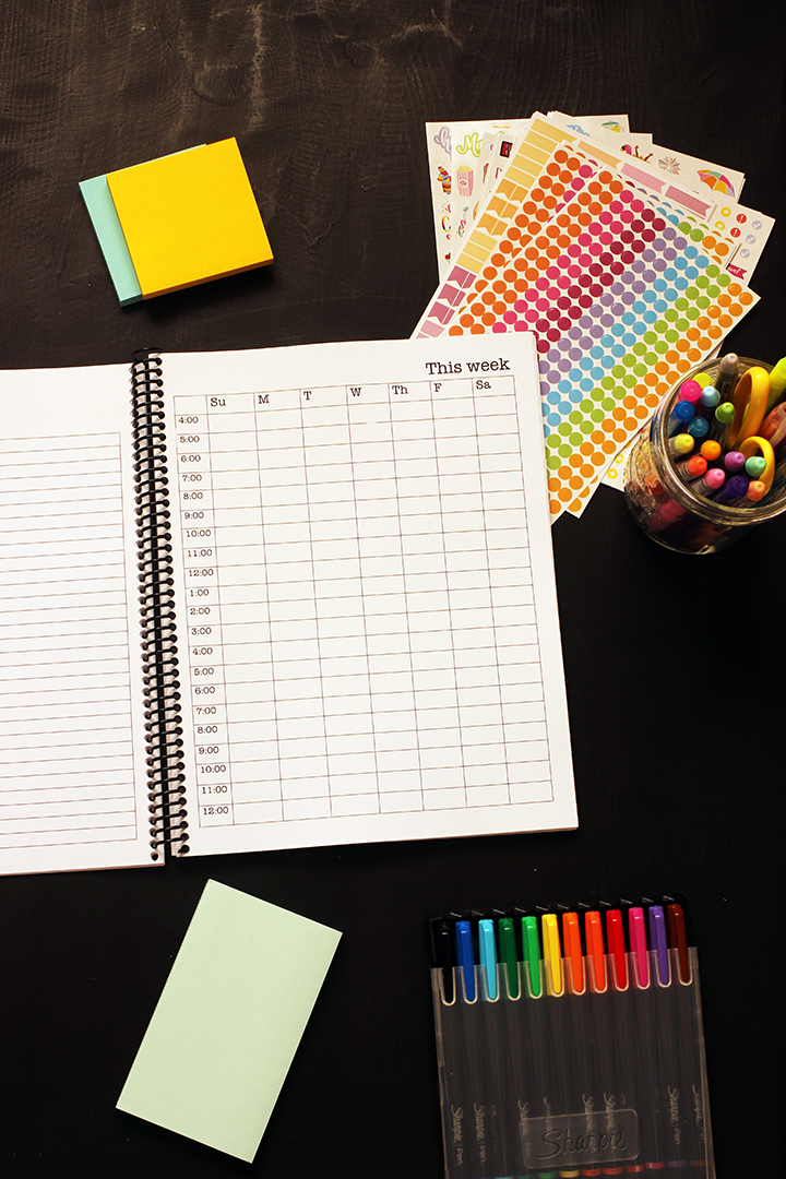 student planner open to weekly page with pens and post-its