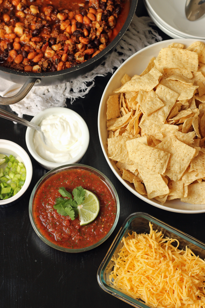 A bowl filled with salsa and other toppings, with chips