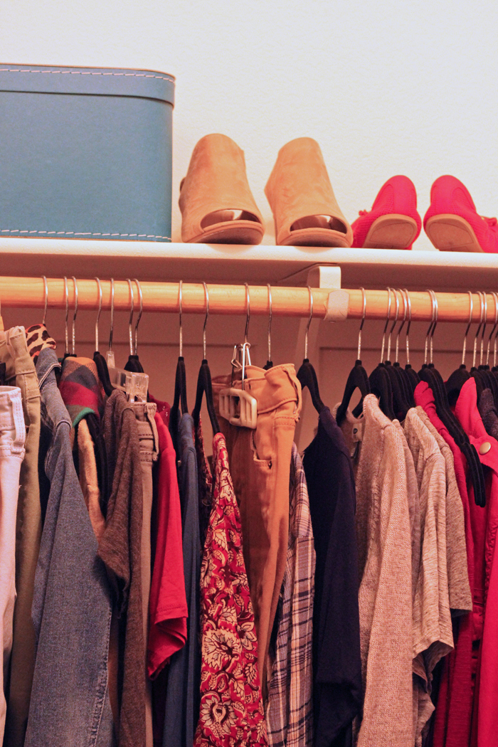 clothes on hangers and shoes on shelf