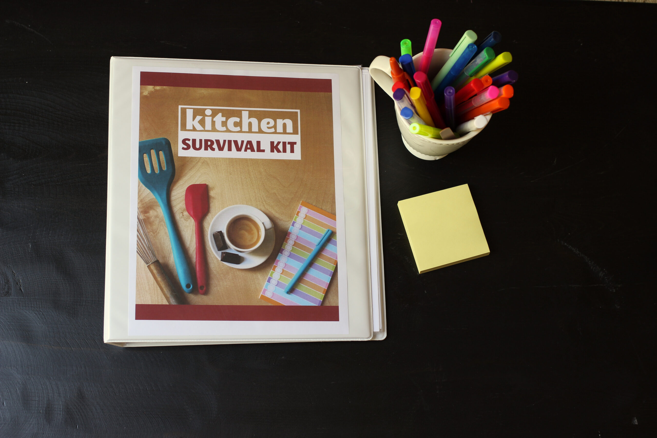 kitchen survival kit binder next to pens and post-its