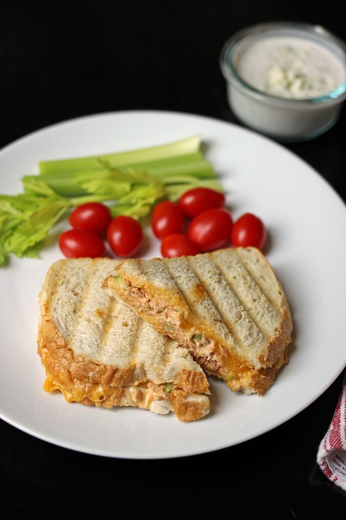 tuna melt sandwich on a white plate with veggies