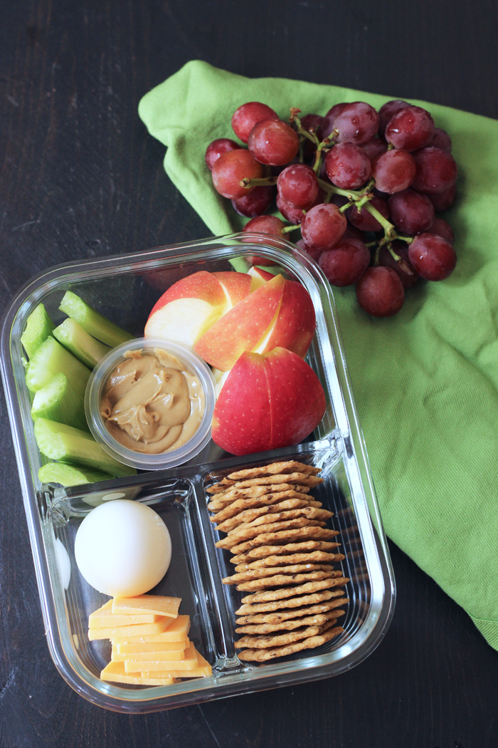 glass divided box with apples, celery, egg, cheese, and crackers