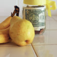 bananas and pear next to jar of money tied with yellow bow