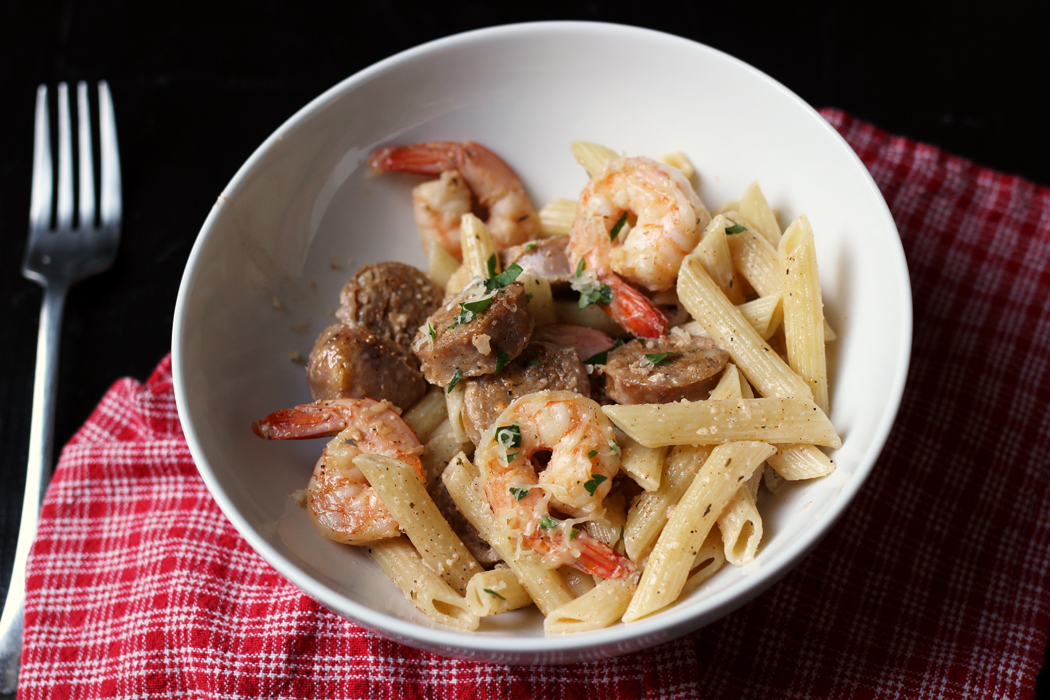 fork and individual bowl of creamy shrimp pasta on red napkin