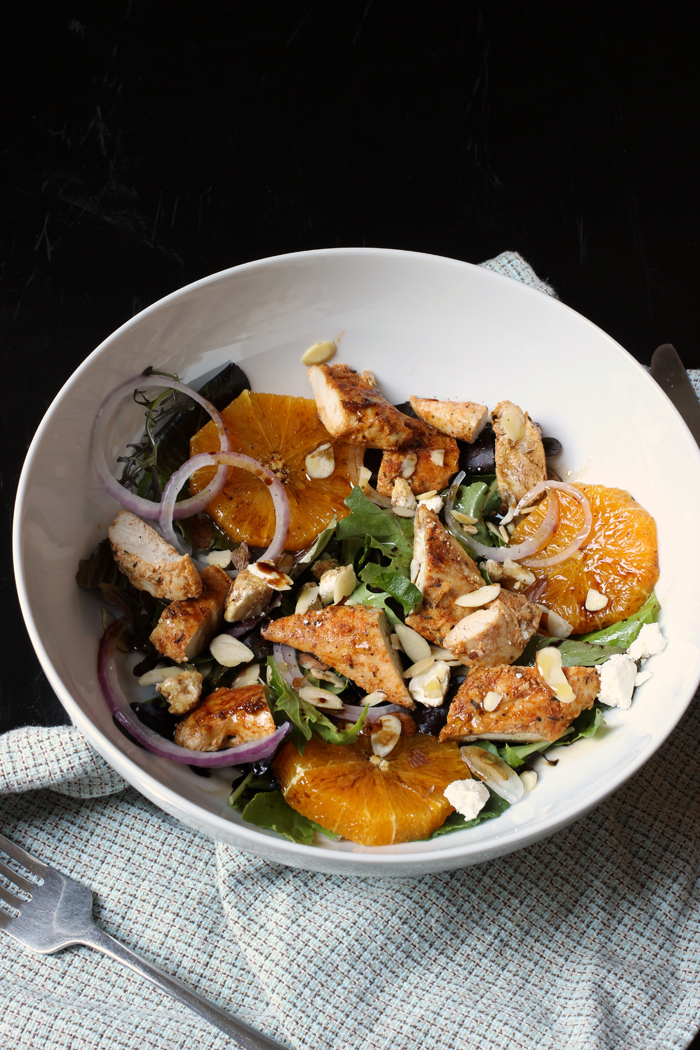 bowl of salad with chopped chicken, orange slices, and feta cheese