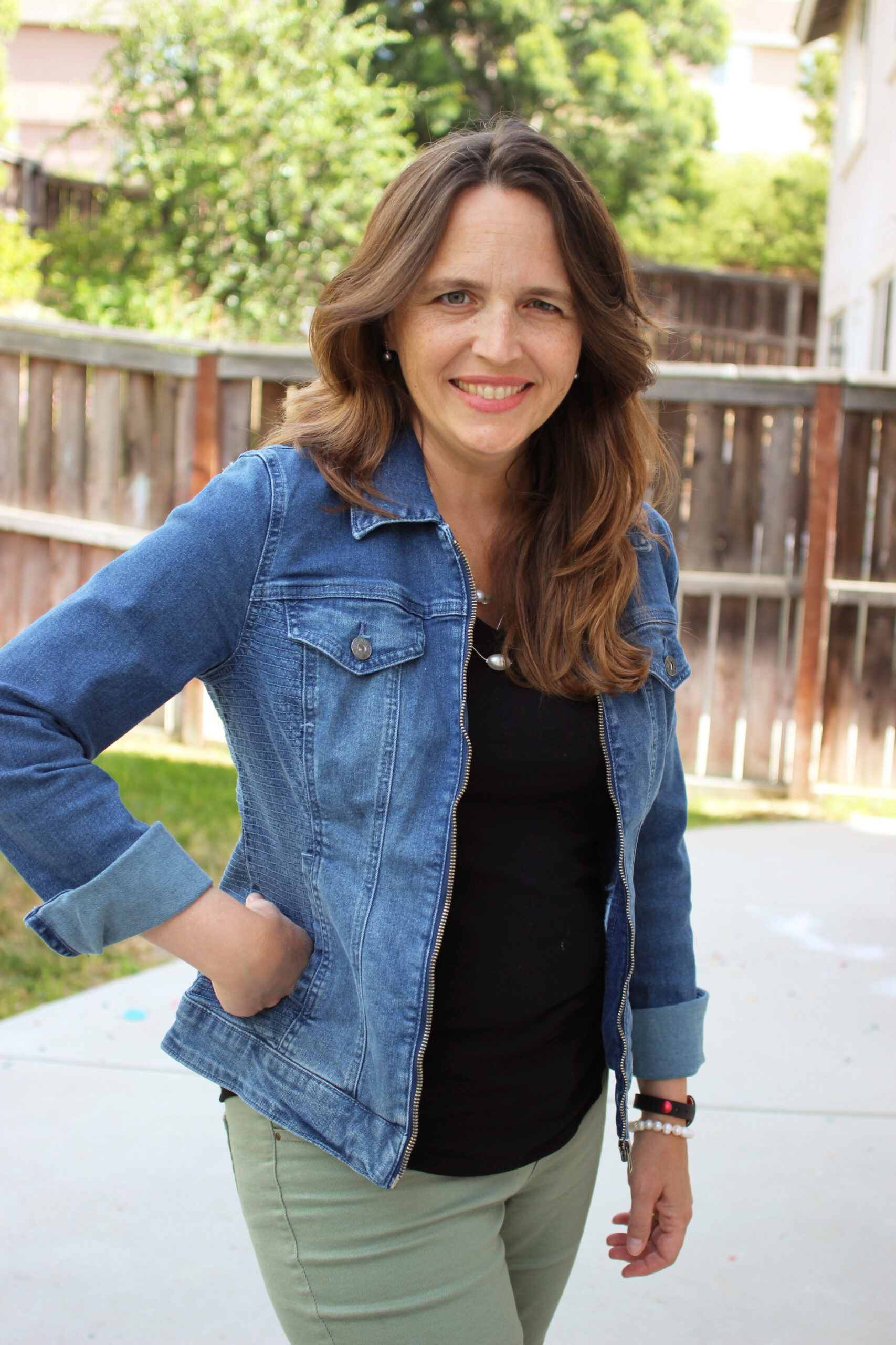 woman in denim jacket with hand on hip