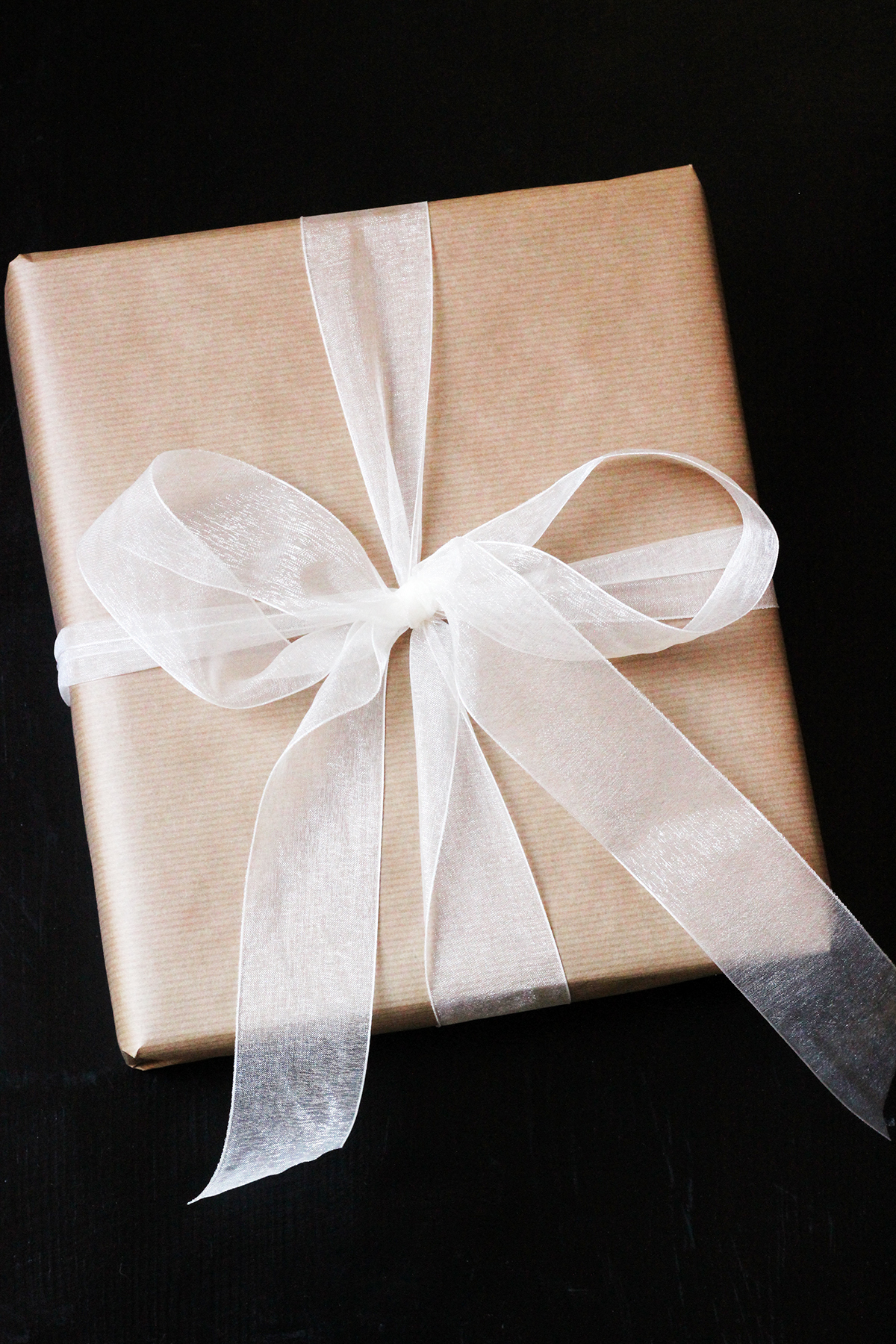 gift wrapped in brown paper and white filmy bow