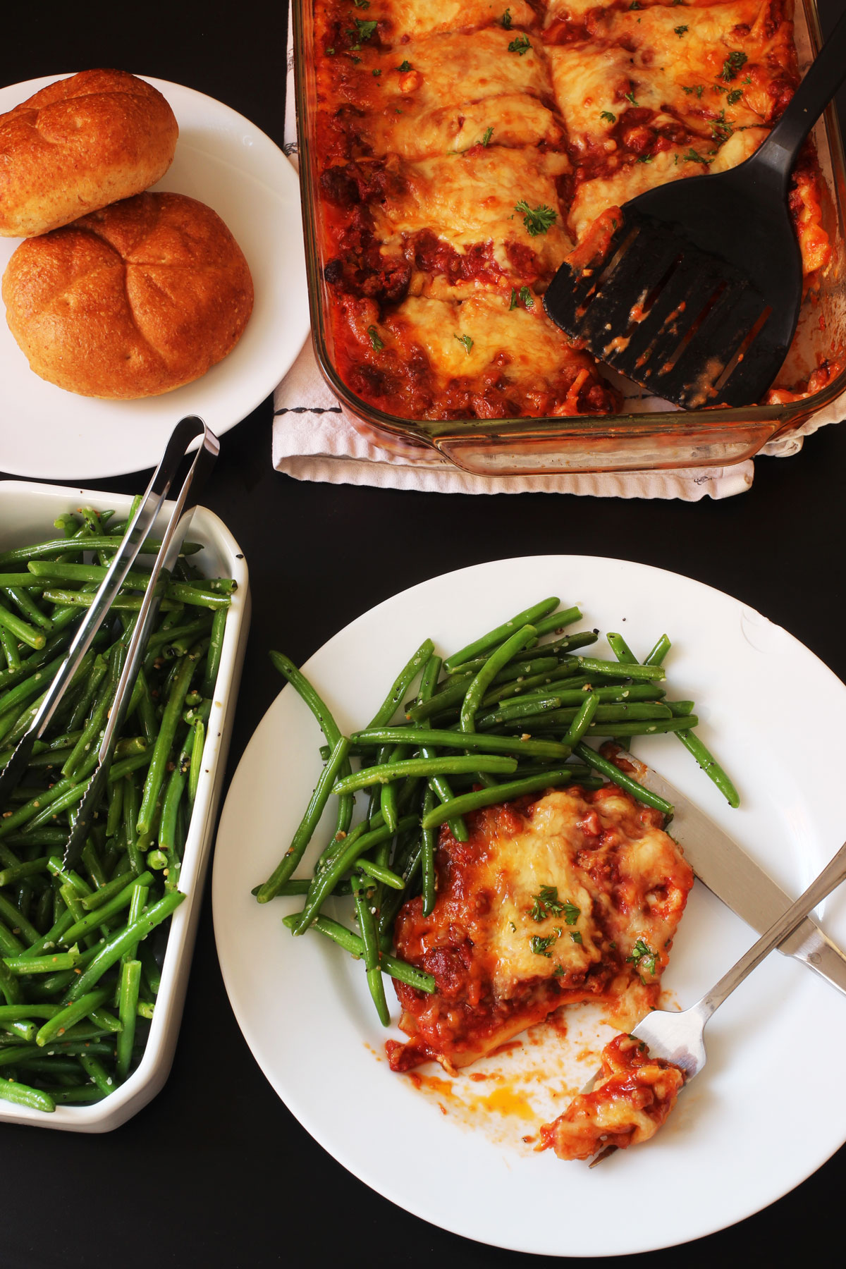 dinner table set with lasagna and green beans